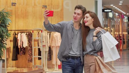 Lovely young couple taking selfies while shopping at the mall together. Cheerful man embracing his girlfriend, taking photos with her using his smart phone. Technology concept Stock fotó
