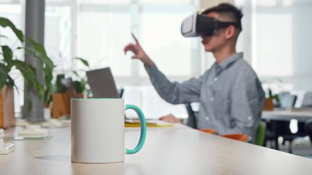 Cup of coffee on the table, man using 3d vr glasses at work on the background. Male entrepreneur trying virtual reality headset at his workplace, copy space. Relax, coffee break concept