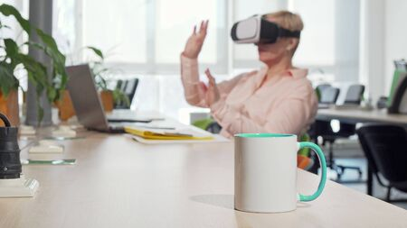 Female entrepreneur using 3d virtual reality goggles at the office. Selective focus on a cup of coffee on the foreground, businesswoman wearing vr goggles on the background 写真素材