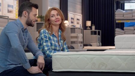 Happy couple shopping for new bed at furniture store. Attractive housewife choosing orthopedic mattress with her husband at furnishings shop. Love, couples, relax, home concept Zdjęcie Seryjne