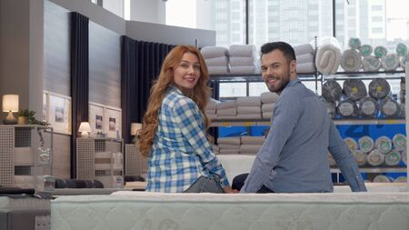 Cheerful couple smiling to the camera, while choosing new bed at furniture store. Beautiful woman and her husband sitting on orthopedic mattress at furnishings shop. Retail concept