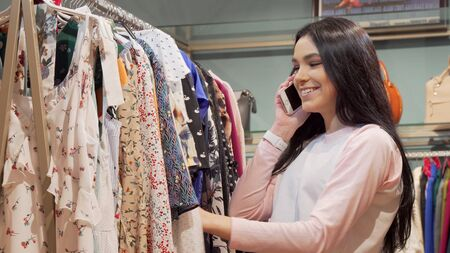 Charming young woman talking on the phone while shopping for clothes. Lovely female customer using her smart phone while checking out dresses on sale. Social, lifestyle concept