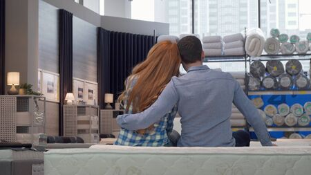 Rear view shot of a couple hugging, sitting on a new bed at furniture store. Lovely couple buying orthopedic mattress together, sitting on a bed, hugging. Love, family, home concept