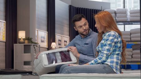 Beautiful couple choosing orthopedic mattress at furniture store together. Handsome man and his lovely wife discussing orthopedic mattress sample. Consumerism concept