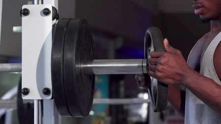 African man putting weight plates on barbell, exercising at the gym. Cropped shot of a ripped male athlete working out at the gym, preparing barbell for weightlifting exercises. 4K footage Stock fotó - 130734158