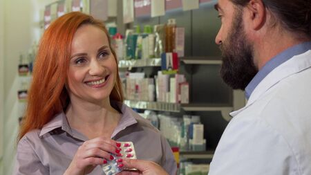 Beautiful woman receiving pills from her pharmacist, shopping at drugstore. Attractive mature female customer buying prescription medicine at pharmacy. Consumerism, health care concept Archivio Fotografico