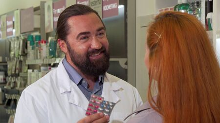 Friendly male pharmacist selling pills to female customer. Bearded handsome mature male chemist working at drugstore, giving blisters of pills to a woman. Health, vitamins concept