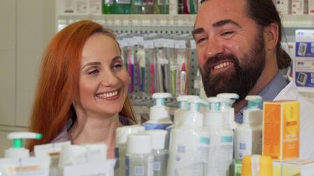 Handsome bearded pharmacist giving his female customer requested product. Beautiful cheerful woman smiling, shopping at the pharmacy. Consumerism, friendly service concept