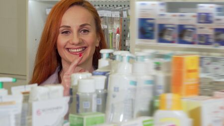 Attractive woman smiling, choosing medical products from the shelf at drugstore. Beautiful woman shopping at the pharmacy. Female customer buying medicine. Retail concept