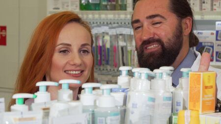 Beautiful woman talking to the pharmacist, while selecting products to buy. Handsome bearded mature chemist working at drugstore, selling medication to customer Archivio Fotografico