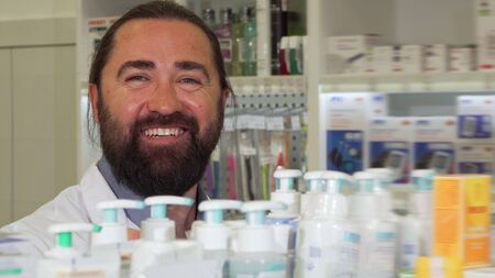Bearded pharmacist smiling to the camera, while working at drugstore. Handsome mature bearded male chemist checking stock in an aisle, working at pharmacy. Job, doctor concept Archivio Fotografico