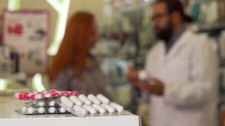 Pills in blister on the foreground, woman talking to the pharmacist on the back. Selective focus on medication packs on the counter, druggist helping his female customer