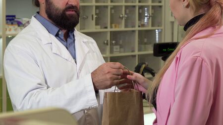 Unrecognizable pharmacist giving shopping bag with medicine to a customer. Cropped shot of a bearded male chemist selling medication to his female client. Sales concept Archivio Fotografico