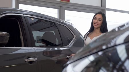 Woman smiling to the camera, while examining cars on sale at the dealership. Gorgeous young woman buying new automobile, looking inside the vehicle. Retail concept Archivio Fotografico