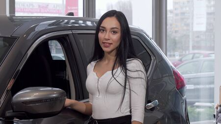 Beautiful woman choosing new car at the dealership. Lovely female customer buying new vehicle at car salon. Attractive woman examining automobile for sale. Driving concept