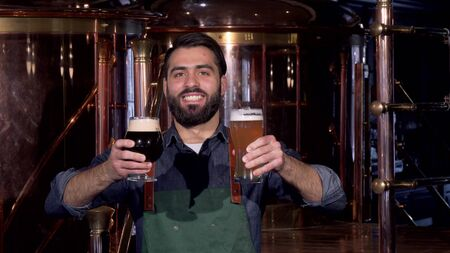 Cheerful professional brewer smiling, holding two beer glasses at his brewery. Bearded beer maker offering freshly brewed delicious craft beer to the viewer. Business, entrepreneur concept Archivio Fotografico