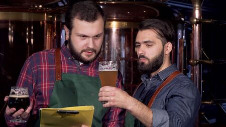 Two male brewers examining delicious craft beer they manufacture together. Bearded brewer talking to his colleague, discussing work at craft beer manufacturing. Brewing concept Archivio Fotografico - 130800511