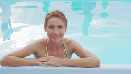 Beautiful happy woman smiling relaxing in the swimming pool. Gorgeous happy woman enjoying hot summer day at the poolside. Tourism, travel, resort concept