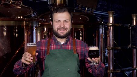 Happy male brewer in apron smiling joyfully holding two glasses of craft beer. Friendly beer maker offering you delicious beer at his brewery pub. Oktoberfest, st patricks concept Stok Fotoğraf