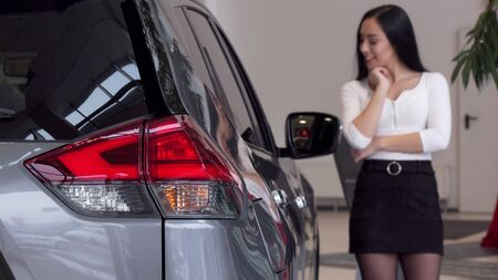 Selective focus on car lights, woman choosing new auto at the dealership. Beautiful woman examining automobile on sale at car salon. Female customer buying car. Drive, safety concept Stok Fotoğraf