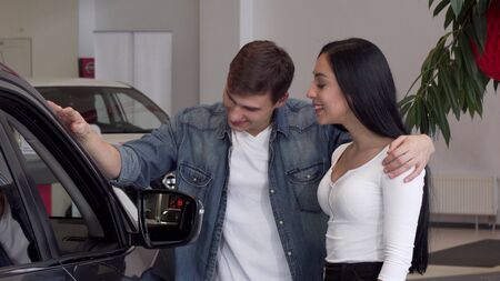 Young couple choosing new car at the dealership, looking inside the automobile. Beautiful woman and her handsome boyfriend buying new auto. Love, travel concept