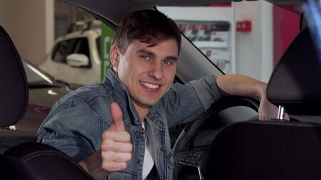 Happy handsome man showing thumbs up, sitting in a new car at the dealership. Cheerful male driver examining new auto, smiling to the camera. Consumerism, insurance concept