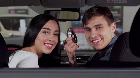 Lovely couple sitting in new auto at the dealership, showing car key to the camera. Beautiful woman smiling at her boyfriend after buying new automobile. Consumerism concept