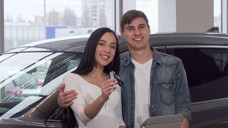 Happy couple hugging, holding car keys at dealership salon. Lovely young couple buying their first new automobile at car dealership. Beautiful woman smiling, holding car keys