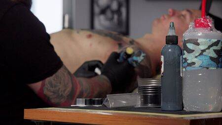 Tattoo artist working at his studio, doing a tattoo on chest of his client. Selective focus on a glass of water black from tattoo ink, tattooist working on background, copy space Archivio Fotografico - 130800571