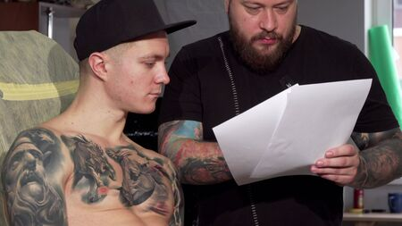Bearded tattoo artist discussing sketches with his male client. Mature professional tattooist working with his customer, showing him drawings before tattooing. Workshop, art concept Stok Fotoğraf