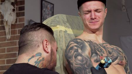 Young man getting painful tattoo on his arm. Sliding cropped shot of a male customer getting tattooed at workshop. Rear view shot of professional tattoo artist working