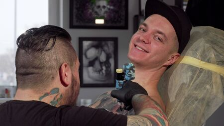 Cheerful young man smiling to the camera, while getting tattooed. Happy man getting new tattoo at the studio, smiling joyfully. Unrecognizable tattooist working with a client