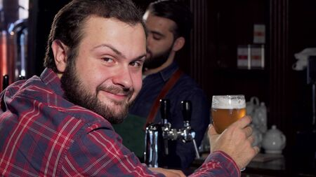 Male customer smiling to the camera, having delicious beer at the pub. Bartender serving delicious craft beer to a male client. Happy man smiling to the camera, enjoying beer at bar