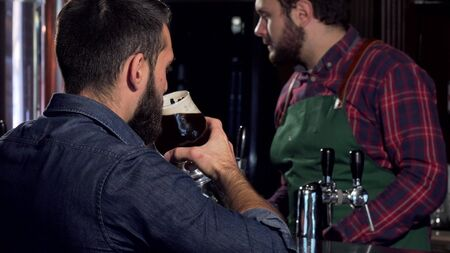 Unrecognizable man drinking delicious craft beer at the pub. Male customer having tasty beer served by bartender at the pub. Professional brewer serving beer to a client