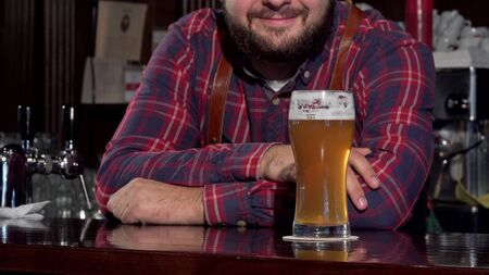 Unrecognizable bartender smiling, putting glass of beer on the counter. Cropped shot of a bartender serving you delicious craft beer in a glass, smiling joyfully. Service, celebration concept