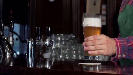 Bartender pouring glass of delicious tasty beer at pub, placing it on the counter. Selective focus on a glass of tasty cool beer on the bar counter, copy space. Celebration concept