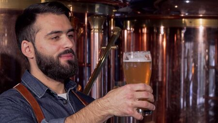 Handsome bearded brewer enjoying smell and taste of delicious craft beer. Professional beer maker tasting freshly brewed beer, working at his manufacturing. Brewing concept Stok Fotoğraf