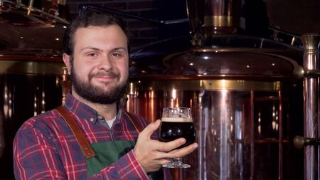 Beer maker drinking delicious dark beer, smiling to the camera. Cropped shot of a professional brewer tasting freshly made beer at his brewery pub. Enjoyment, celebration concept