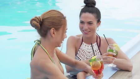 Two gorgeous women talking and drinking cocktails at the swimming pool. Beautiful woman clinking glasses with her friend, relaxing in the swimming pool. Travel concept