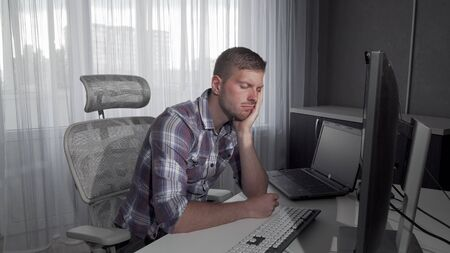 Handsome man falling asleep in front of his computer. Attractive male student looking tired after studying. Computer programmer falling asleep after night of working 4k footage