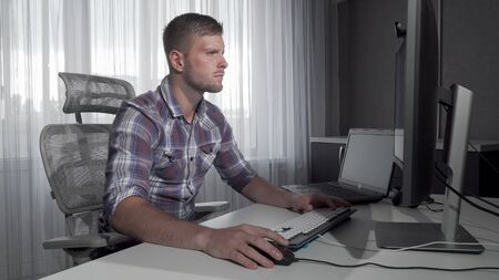 Handsome IT office worker using two computers working on a project. Young computer programmer working online. Attractive man studying online. Internet concept Stock fotó - 130801242