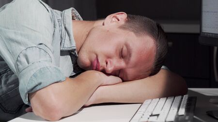 Man sleeping on the table in front of the computer. Sliding cropped shot of a male IT office worker smiling in his sleep, resting on the desk in front of computer. Overworking concept Archivio Fotografico - 130787154