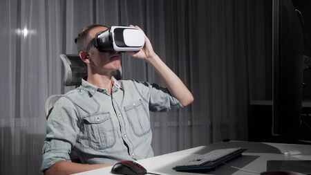 Young man using virtual reality 3D glasses late at night. Handsome man sitting in front of his computer, trying vr headset, looking overwhelmed. Technology, new experience concept Stok Fotoğraf