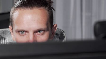 Sliding cropped shot of a male eyes looking at computer monitor. Unrecognizable man working online, using computer late at night. Technology, connection, internet using concept