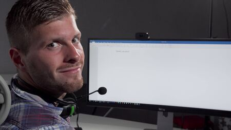 Handsome call center operator smiling to the camera after typing on his computer. Cropped rear view shot of a male customer support manager wearing headset with microphone