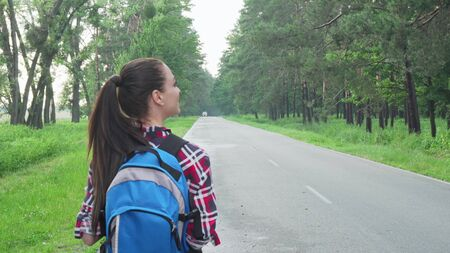 Happy female backpacker admiring nature, walking on countryside road. Rear view shot of a cheerful woman enjoying backpacking, looking around. Tourism, vacation concept Archivio Fotografico