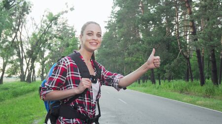 Charming woman with backpack hitchhiking on countryside road. Beautiful female traveler catching a car on the road, enjoying backpacking. Tourism, nature, lifestyle concept Archivio Fotografico