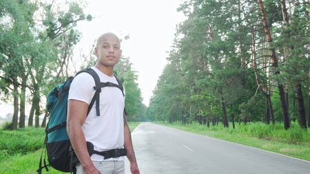 Handsome African man hitchhiking on countryside road with backpack. Attractive cheerful male hitchhiker catching a ride during his trip across country 스톡 콘텐츠