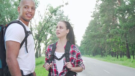 Happy beautiful woman enjoying travelling and hitchhiking with her boyfriend. Multiracial couple hitchhiking on countryside road, travelling together. Getaway, nature, love concept Stock fotó - 130732080