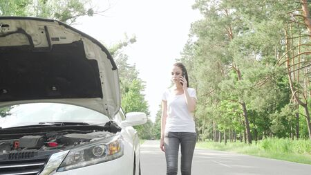 Beautiful woman looking under the hood of her broken car on countryside road. Young female driver examining machinery of her car, waiting for tow truck service help on the road Archivio Fotografico